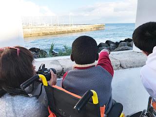 Dois alunos e uma técnica do Farol Museu observam e conversam sobre o mar