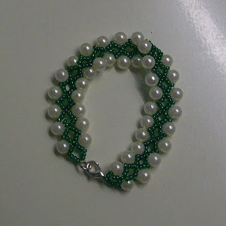 A bracelet of green seed beads and white pearl beads