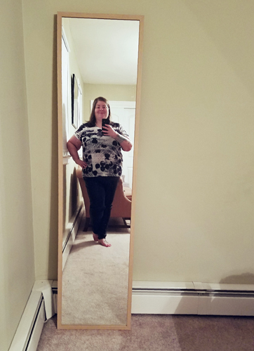 image of me, a fat middle-aged white woman, standing in a mirror wearing black trousers and a black-and-white patterned short sleeve top