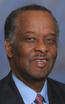 Headshot of a middle-aged Black man with a receeding hairline. He is wearing a suit and tie and his short hair is graying at the temples.