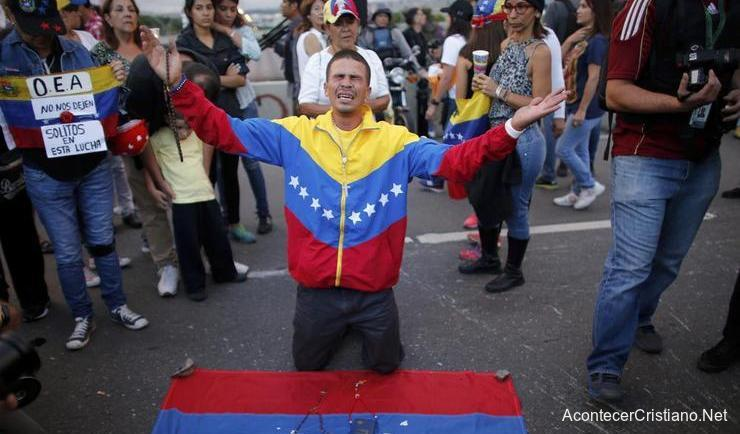 Venezolano orando ante la crisis en su pías