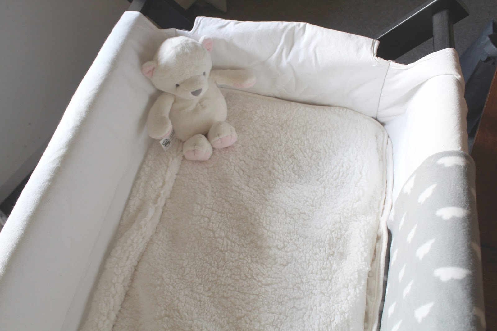 close up of baby's crib with soft blanket and teddy