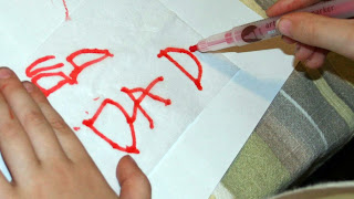 """A child writing \""""Dad\"""" on a piece of paper to design their own candle"""