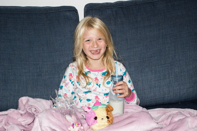 A grinning 7 year old on the sofa in PJs with a blanket and soft num nom and smoothie