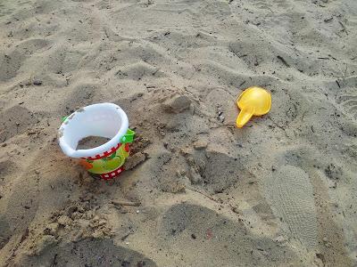 Sandkasten mit Schippe und Eimer