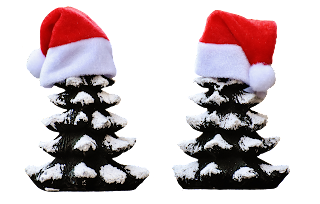 Twin snow-covered Christmas trees topped with Santa caps.