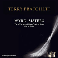 Wyrd Sisters audiobook cover. A silvery broom is propped up against the right-hand side, with a crown hidden beneath. The cover is solid black.