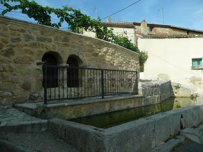 arcos de la fuente, barandilla y pilón. Por encima de la fuente se ven parras