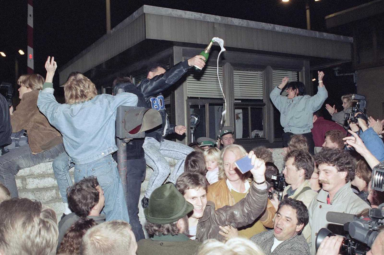 East and West Berliners mingle as they celebrate in front of a control station on East Berlin territory, on November 10, 1989, during the opening of the borders to the West following the announcement by the East German government that the border to the West would be open.