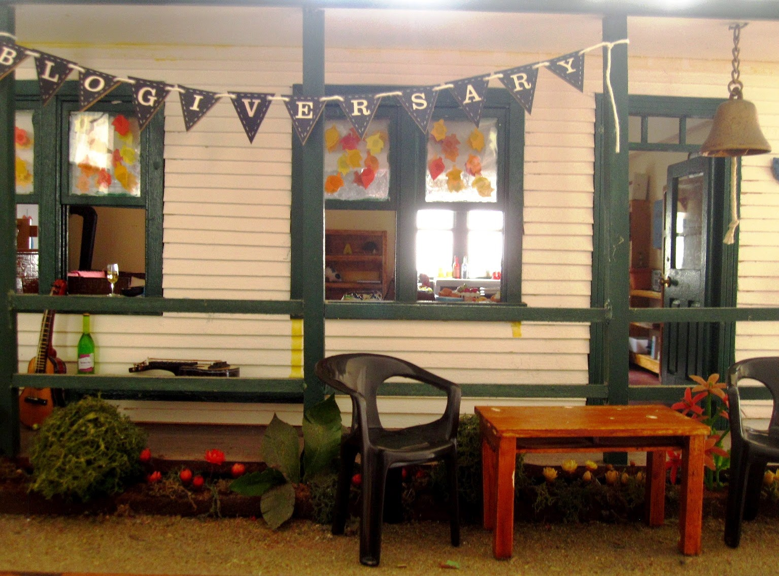 Miniature dolls' house school with bunting reading 'blogiversary' tied to the front verandah.