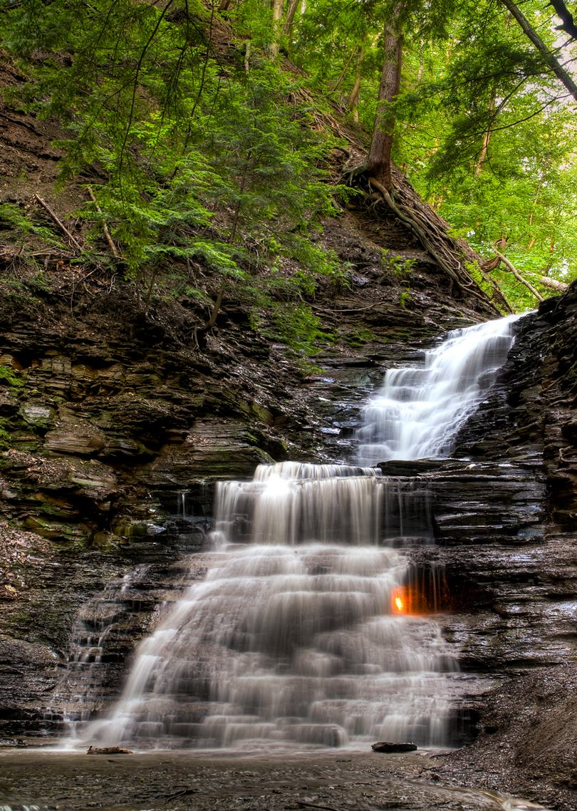 A mysterious flame sitting behind a small waterfall located in the Shale Creek Preserve in Western New York, USA. A small alcove at the waterfall's base emits natural gas, which can be lit to produce a small flame.
