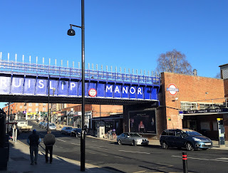 Pic of Ruislip Manor station and railway bridge with its name from opposite side of street
