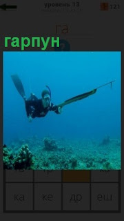 Под водой аквалангист с гарпуном охотится на морских обитателей