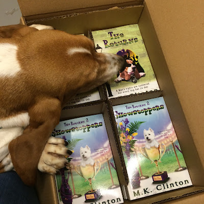 Basset looking at box of The Returns paperback books