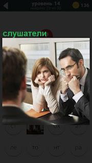 За столом сидят мужчина и женщина в качестве слушателей