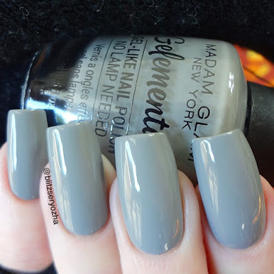 "A swatch photo showing two coats of Madam Glam ""Souvenirs,"" a light grey creme polish"