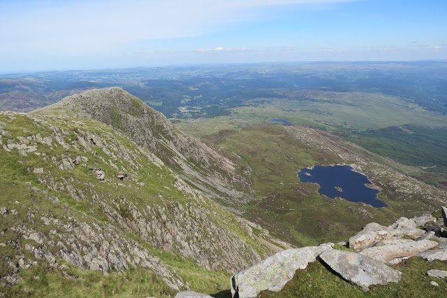 On the left, the rocky north-eastern ridge of Moel Siabod, on the right the lake Llyn-y-Foel. North Wales stretches out to the horizon beyond.
