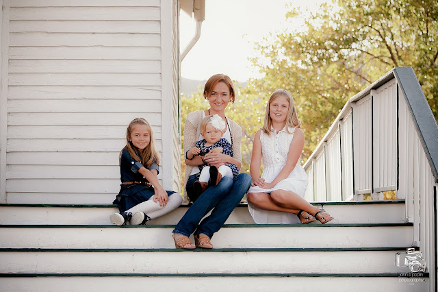 A young mom sits with her three young girls for a photo in Colorado