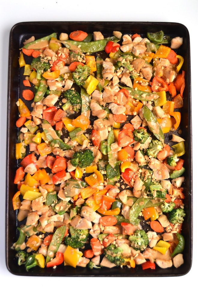 Sheet Pan Peanut Chicken and Vegetables is a simple dinner cooked all on one pan for less dishes and work! Ready in 30 minutes including broccoli, bell peppers, carrots and pea pods all covered in a flavorful peanut dressing! www.nutritionistreviews.com