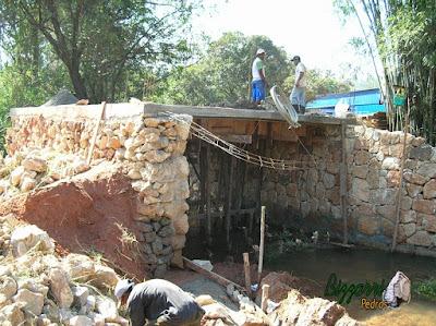 Construção do muro de pedra com pedra bruta para a base da construção da ponte de concreto na entrada da empresa em Atibaia-SP.