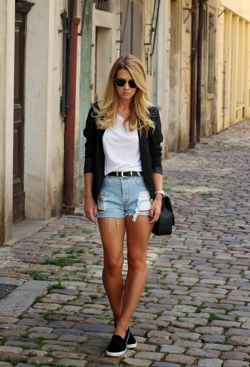 She is wearing black blazer, white, top, denim shorts and black slip on sneakers