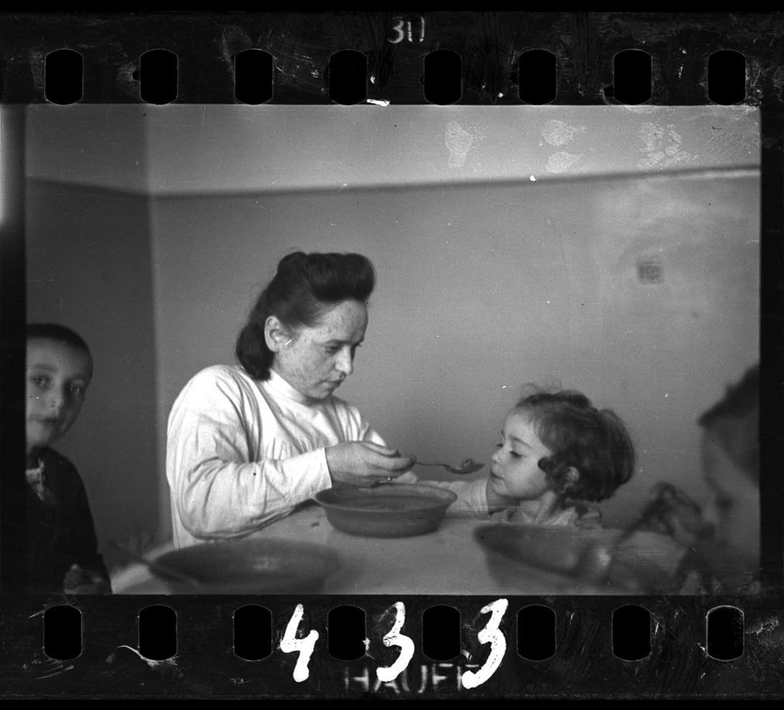 A nurse feeding children in an orphanage.