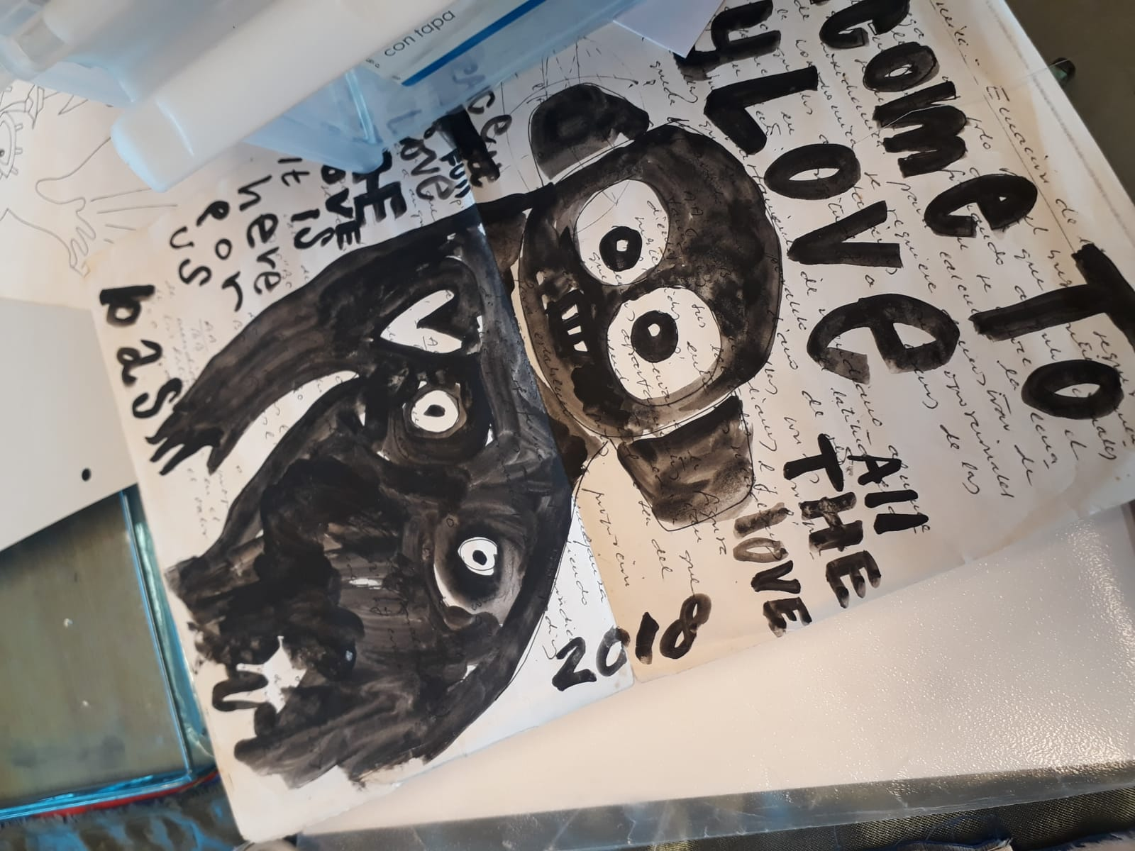 "This picture shows a drawing or sketch for one of Bas Kosters' tapestries, which he made in 2018. It depicts a black human-like figure, with the words ""come to my love"", ""all the love"", ""2018"" surrounding it, and other expressions that are obsured by another piece of paper."