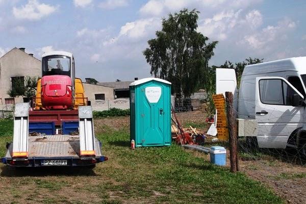 budowa domu - przygotowanie do budowy, koparka, toaleta i bus z narzędziami