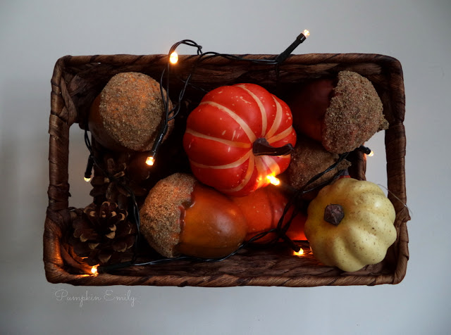a basket with pumpkins, acorns, pine cones, and a string light in it