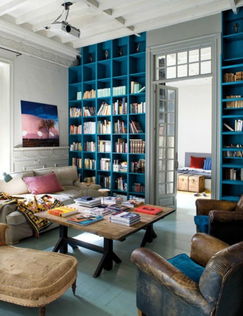 Coastal living room with library bookshelves painted bright aqua blue