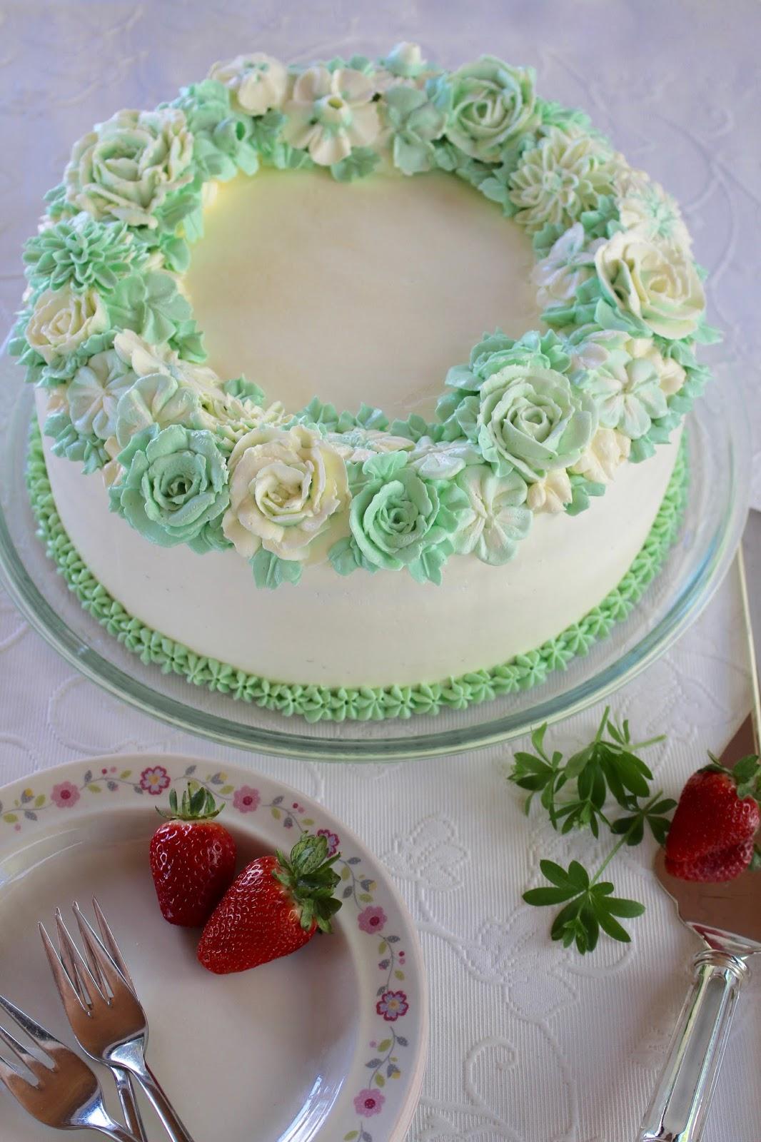 Erdbeer-Waldmeister-Torte mit einem Kranz aus Buttercreme-Blüten