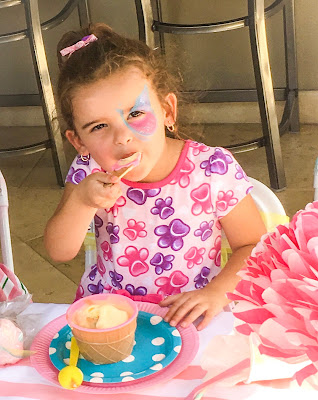 Little girl in a pink dress eating ice cream