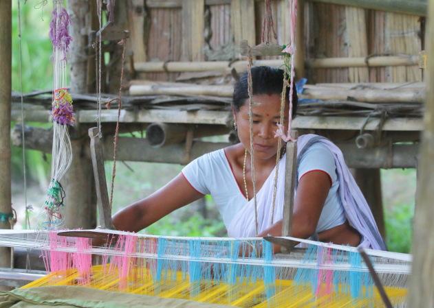 Portrait of Mishing tribal woman weaving on her traditional loom, Panbari village, Assam