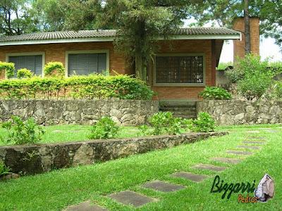 Execução do caminho do jardim com pedra folheta de granito tamanho 40x60 cm com os muros de pedra, a casa de tijolo a vista em sítio em Bragança Paulista-SP.