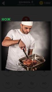 На подносе у повара мясо, которое он разрезает ножом на кусочки