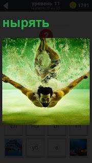 Мужчина ныряет в воду, опускаясь на самое дно. Вокруг него брызги и близко расположено дно