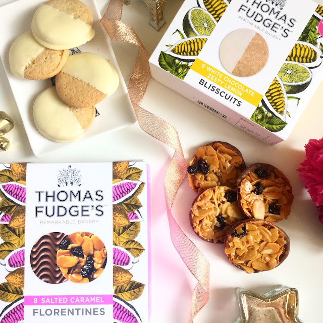 flatlay - top left corner, lemon and white chocolate biscuits on a trinket dish, the box next to it on the right, bottom left corner is the box of florentines and to the right is a selection of them next to it. Flowers in space on the right and a ribbon running through the middle of the photo