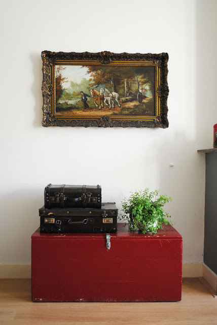 Boven een oude rode dekenkist hangt een groot oud schilderij van twee paarden die een boomstam voort trekken door het bos. Op de dekenkist staan een groene plant en twee oude bruine koffers.