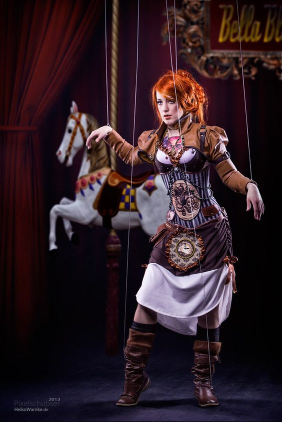 Women's halloween or steampunk costume: steampunk marionette doll. She has puppet strings and wearing steampunk clothing: corset, bolero jacket, boots and skirt.