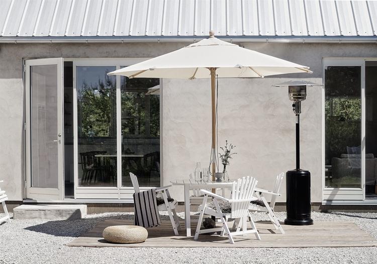 terraza-blanca-sombrilla-sillas-madera-conjunto-terraza-blanco-puerta-cristal-puff-estufa-decoracion-nordica
