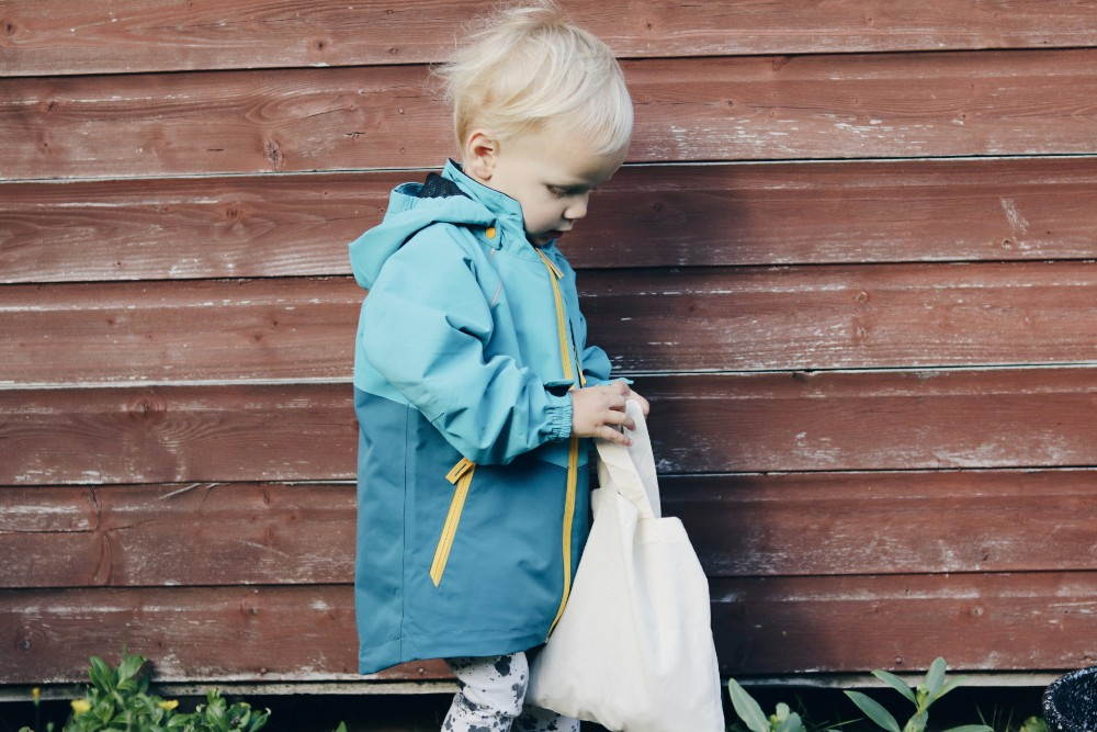 blonde-toddler-boy-wearing-blue-coat-holding-canvas-bag-walking-past-brown-fence