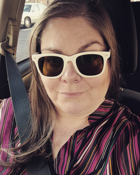 image of me in the car, wearing white sunglasses and a red and black striped shirt, with my hair down