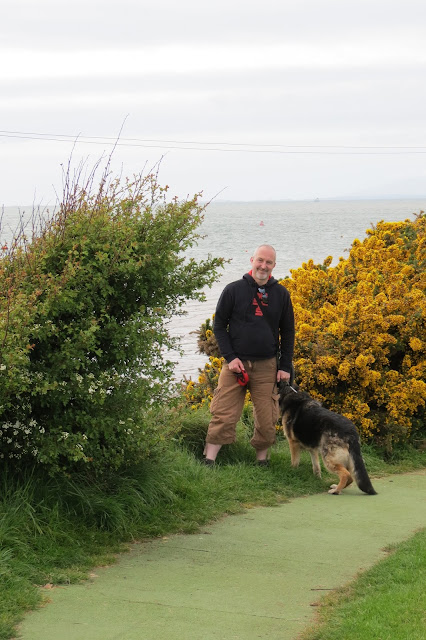 A picture of me and our dog standing by a gorse bush with the sea in the background.