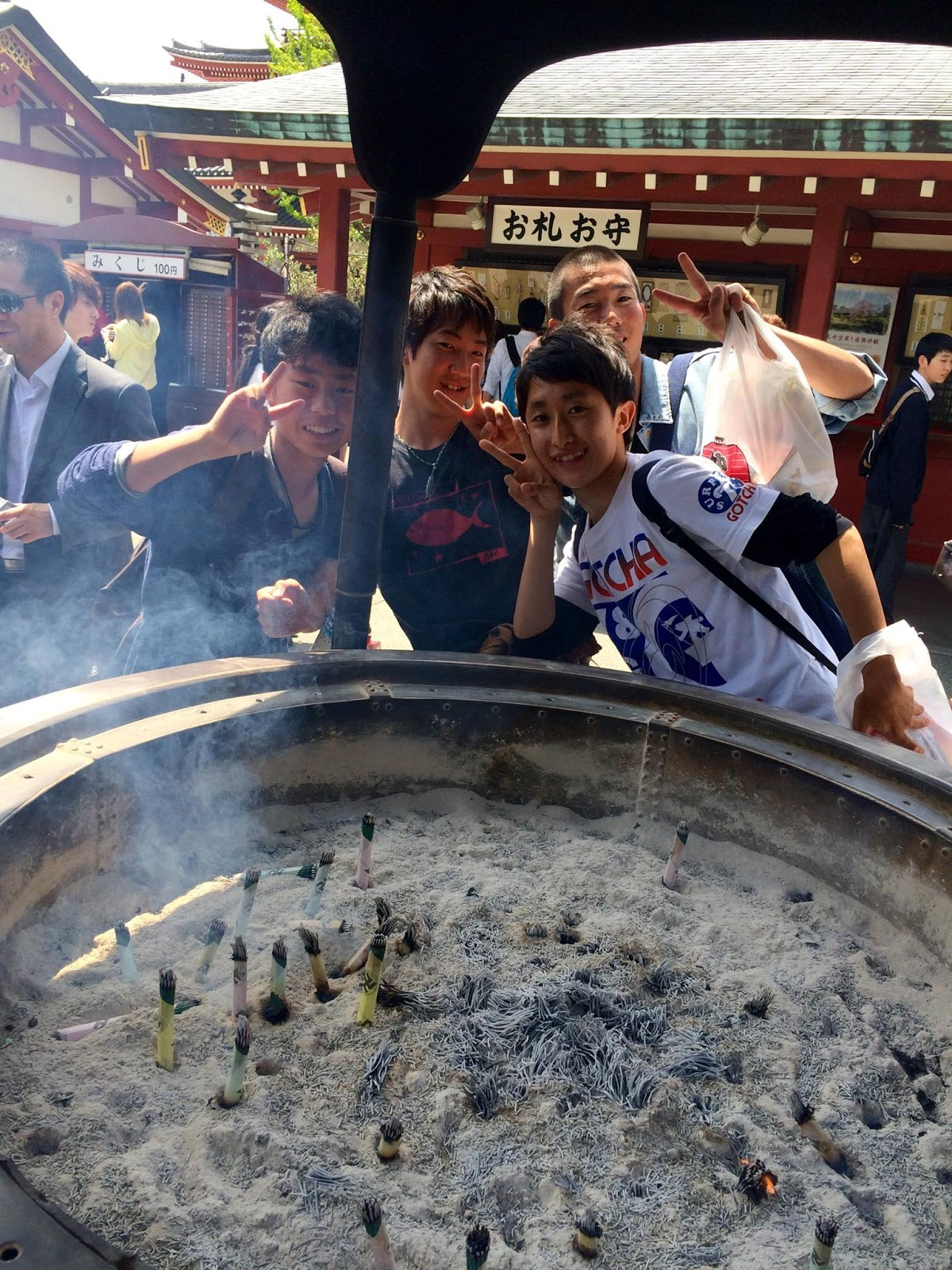 Teenage students in front of a large cauldron of incense at Senso-ji temple. People waft the fumes over their bodies to bestow good health - April 2015