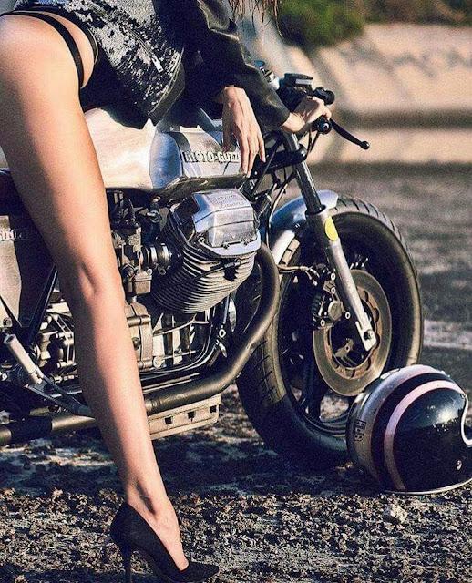 Girl sits astride a custom Moto Guzzi Cafe Racer