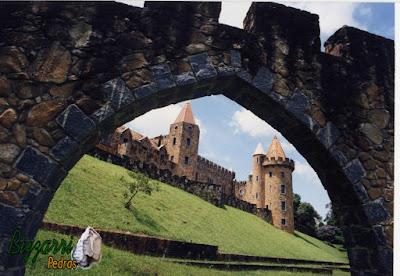 Castelo de pedra, com a torre de pedra, construído com pedra moledo nessa cor mesclada.