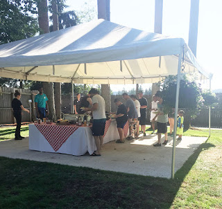 Several students and guests serving themselves at outdoor BBQ buffet at Wild Waves