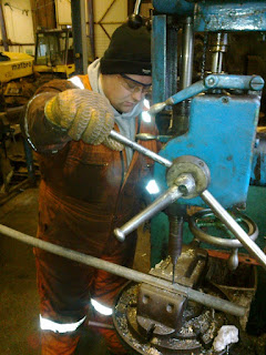 Ryan drilling a pipe for Twizell's ashpan water