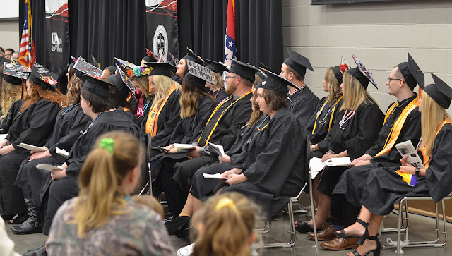 Group of students, seated, in graduation robes and caps