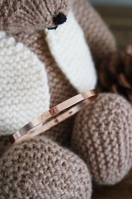 a knitted brown teddy bear holds a rose gold bangle